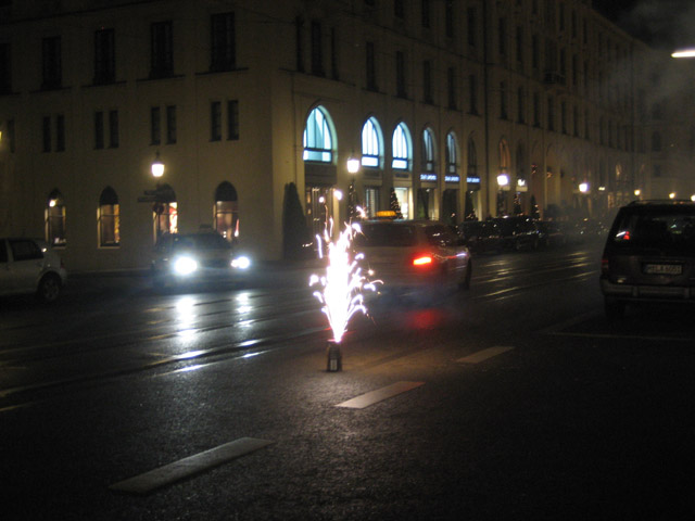 We left the restaurant at about 11:45, heading towards one of the many public squares in Munich. Instead of the highly calculated, lawsuit-proof fireworks displays we have in the U.S., Germany prefers to let its citizens take their lives into their own hands. The general populace takes over the streets on New Year's Eve and sets them on fire. Everyone, from little kids to old men, come out with their displays. Those with smaller affairs stay on the side streets, basically throwing firecrackers at passersby.